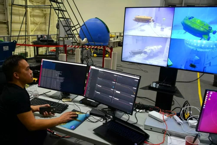 攝影:Evan Ackerman。圖:(上)HMI的工程師在檢查Aquanaut的�部(主要的感應器都裝在�部),為下水做準備。(下)傳統的無人水下航行器需要技術人員控制它的傳感和運算系統,以完成自動操作,它可以在技術人員的監督下執行任務而不需要人的直接控制。