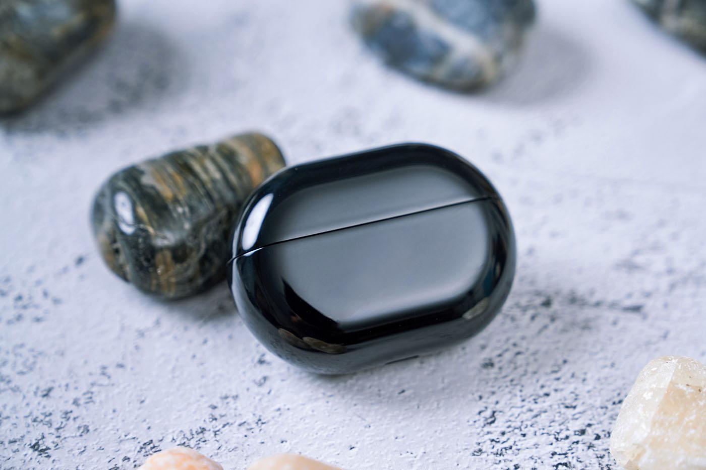 充電盒另一面則是十分純粹的黑色鏡面烤漆,看來更像一塊精緻的鵝卵石寶石,晶瑩剔透。