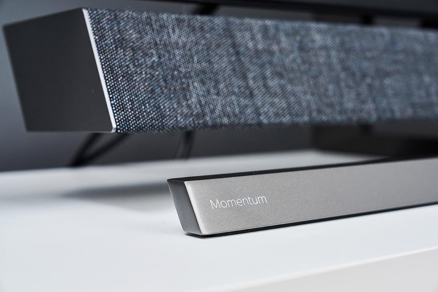 近距離拍攝 559M1RYV 一體式底座,同時也能看清音響系統面網質感,首先底座上有著這款顯示器系列名稱「Momentum」,精細小巧的字體,相當漂亮,而音響面網則是採用編織設計,中灰度的色系,搭配銀灰螢幕底座,顯示出精品質感。